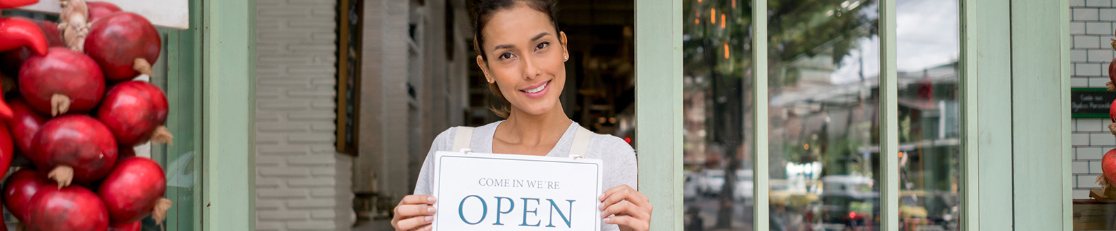 Female business owner holding open sign